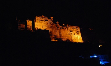 Taragarh Fort is lit up at night.