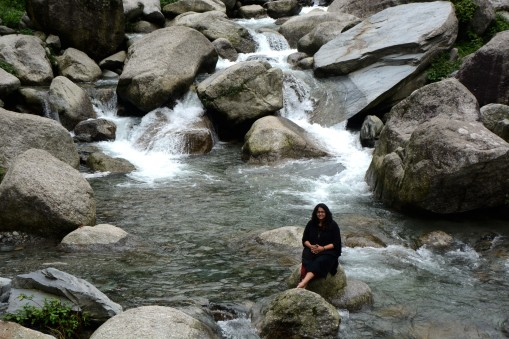 She sat there while water tumbled off rocks all around her.